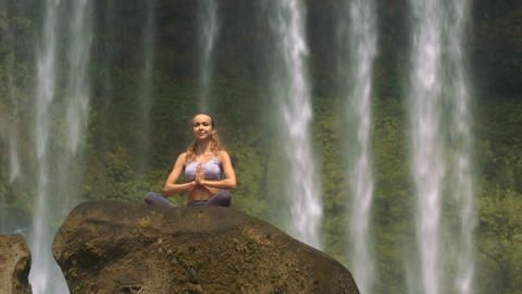 Woman Sits in Lotus Pose on Stone against Water GIF