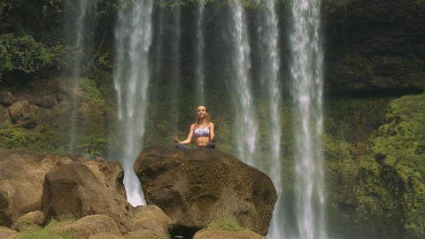 Blond Lady Relaxes in Yoga Pose on Waterfall Rock Footage
