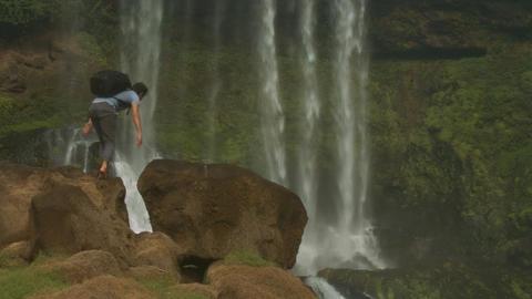 Tourist with Black Backpack Climbs on Huge Rocks GIF