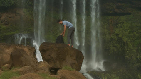Guy with Backpack Stands on Rock Drinks Water by Waterfall Footage