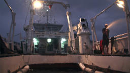 Man washes the submarine, that comes back to the ship at nigh in Pacific Ocean Footage