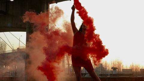 Elegant woman in red dress dancing with red smoke near abandoned bridge Footage