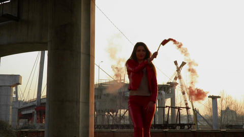 Beautiful woman in red costume dancing with red smoke near abandoned bridge Footage