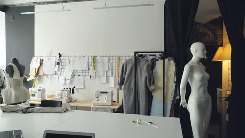 Pan shot of light clothing design studio with large tailor's desk, mannequins Footage