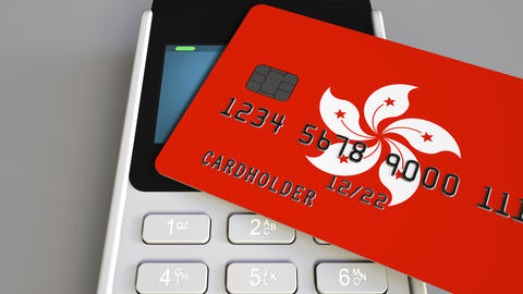 Payment or POS terminal with credit card featuring flag of Hong Kong. Retail Footage