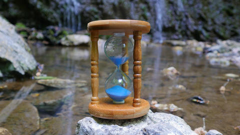 Hourglass on the Background of a Mountain River Footage