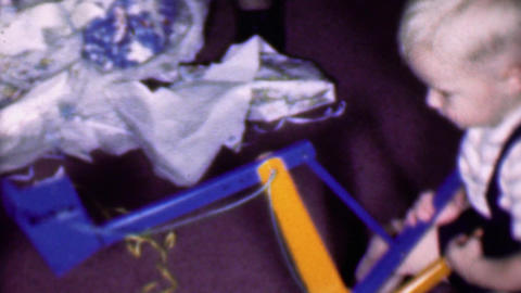 1957: Boy playing Christmas wrapping paper crane digging toy Footage