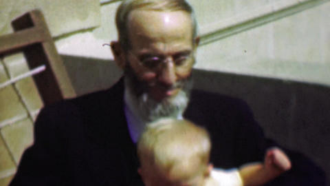 1958: Sharply dressed old grey bearded grandpa holds baby boy Footage