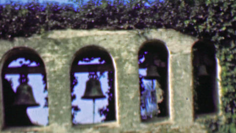 1958: Ivy wrapped ancient church walls hanging bells toll for none Footage