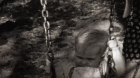 1961: Mother helps baby swing thick chained sturdy made Footage