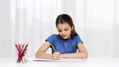 happy girl drawing with colour pencils at home Footage