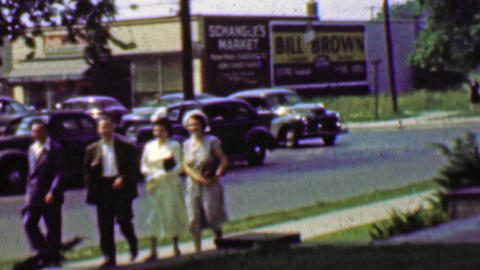 1961: Family coming home from church busy classic car traffic Live Action