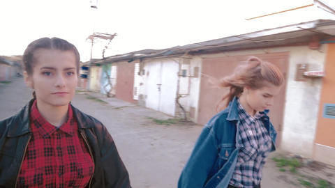 two girls walking around holding hands in the ghetto garages. possibly lesbians Footage