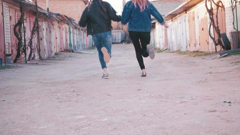two girls running around the garage Footage