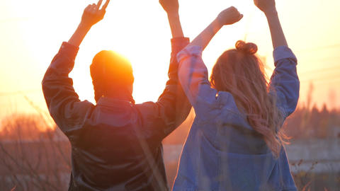 two young women admire the sunset lifting their arms up. Hope Trust, Love Footage