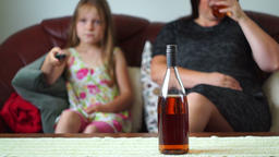 Mother is Drinking Alcohol and is watching Tv with her daughter Footage