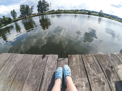 A girl in blue shoes sits on wooden pier near the lake river フォト