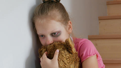 Sad girl cuddles up in a teddy bear and sits on the stairs. Domestic Violence Live Action