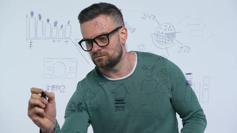 Man draws various growth charts, calculating prospects for success in a modern Footage