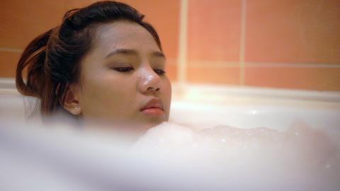 Young Woman blowing foam in bath slowmotion Footage