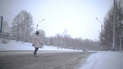 Young Woman crossing the Road in winter. Slowmotion Footage