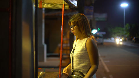 Young Woman buying in street stall at night Footage