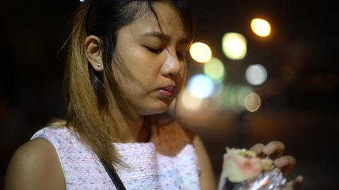 Young Asian Woman eating kebab Footage