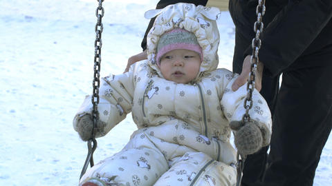 Baby girl sitting on swing in winter Footage
