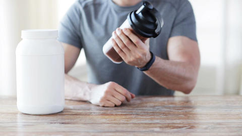 close up of man with protein shake bottle and jar Footage