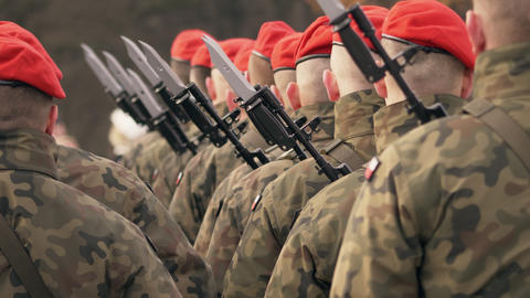 Soldiers in red berets with guns stand with their backs to the camera Footage