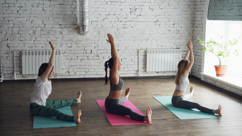 Flexible girls are doing yoga practicing wide-angle seated forward bend in loft Live Action