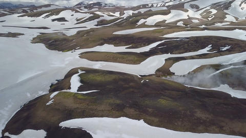 Aerial view of dramatic clouds over snowy volcanic mountains in Iceland Footage