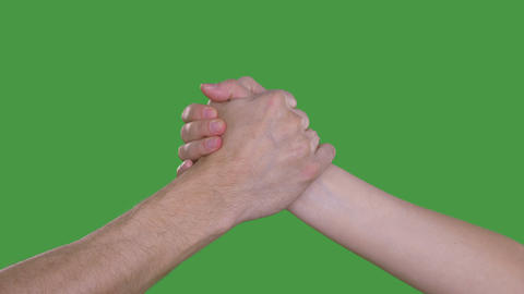Two hands joining together on green screen. Friendship handshake Footage
