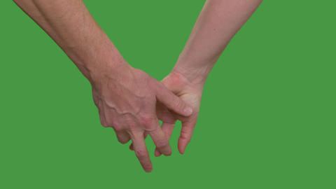 Couple holding hands in lock, cropped view. Keyed green screen Footage