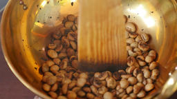 Coffee beans roasting in brass pan, Thailand Live Action