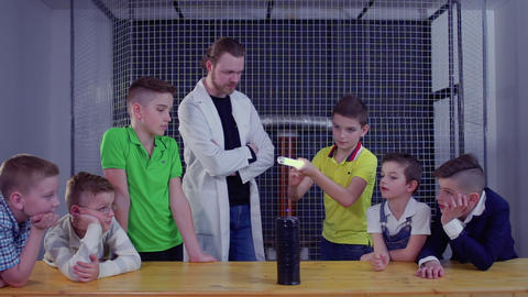 Group of children explores Tesla coil using electric lamp over the it Footage