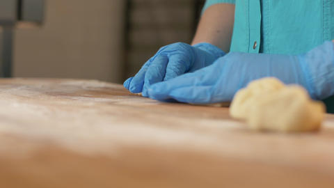 Baker hand making balls from dough for patties on wooden table in bakery shop Footage