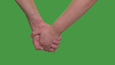 Male hand holding female hand isolated on green background close up Alpha Footage