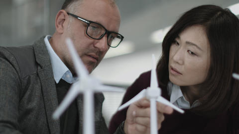 Business people examining wind turbine models in office Footage