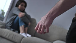 Concept of domestic violence in family, male fist afraid Asian woman sitting on Footage