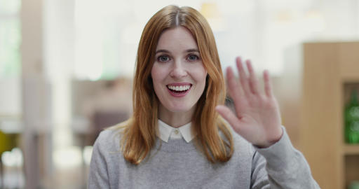 Portrait of female entrepreneur waving to camera in a modern shared workplace Footage