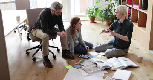 Overhead shot group of designers discussing ideas with paperwork on office floor Footage