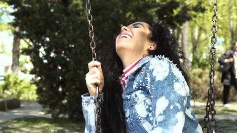 Happy brunette swings on swing in park Footage