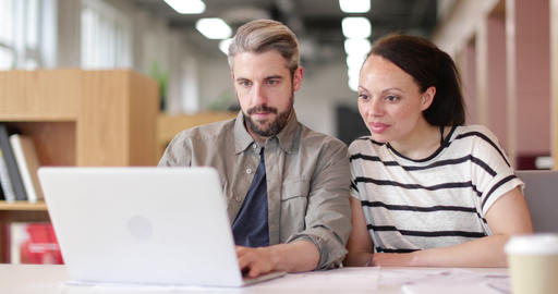 Coworkers looking at a laptop together Footage