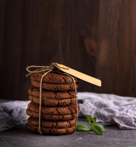 a stack of round chocolate cookies tied with a rope フォト