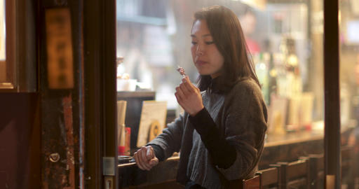 Japanese woman in restaurant eating and looking out of window. Tokyo, Japan ビデオ