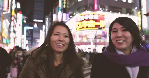 Japanese female friends walking on street in Shinjuku at night, Tokyo, Japan Footage