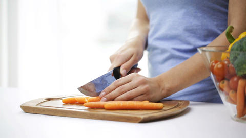 smiling young woman chopping vegetables at home Footage