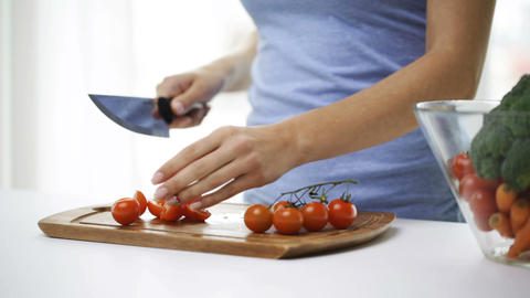 close up of young woman chopping tomatoes at home Footage