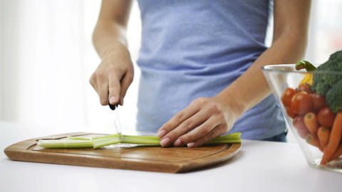 close up of young woman chopping celery at home Footage